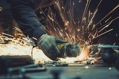 Glühender Fluss von Funken um einen Winkelschleifer, beim Schnitt eines Stückes des Stahlrohrs leiten auf eine Arbeitsfläche Stockbild
