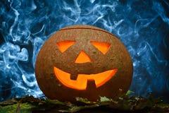 Glühender Halloween-Kürbis und blauer Rauch Stockfotos
