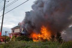 Glühender Hausbrand des Feuerwehrmannkampfes Stockfoto