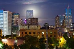 Glühender Mond steigt hinter die Denver-Skyline Stockfotos