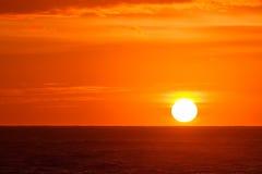 Glühender orange Sonnenaufgang über Meeren Stockfotos