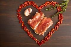 Glühender Pfeffer wird in Form von Herzen gezeichnet Eine Niederlassung des Thymians, eine Knoblauchzehe Sandwiche gemacht vom ha stockbilder