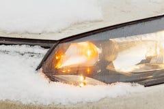 Glühender Scheinwerfer des Schnees bedeckte Autonahaufnahme Lizenzfreie Stockfotos