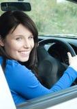 Glühender weiblicher Jugendlicher, der in ihrem neuen Auto sitzt Stockfotografie