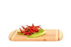 Glühendes Paprika peper, das auf grünem Salat liegt Lizenzfreie Stockbilder