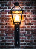 Glühendes Straßenlaterne auf Backsteinmauer Stockfoto