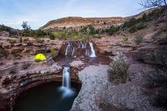 Glühendes Zelt nahe felsigem Wasserfall in Süd-Utah Stockbilder