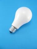Glühlampe auf blauem Hintergrund. Lizenzfreie Stockbilder