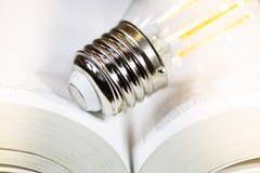 Glühlampe auf einem Buch lizenzfreies stockfoto