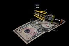 Glühlampe auf Geld Lizenzfreie Stockbilder