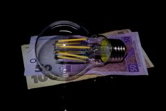 Glühlampe auf Geld Stockfotografie