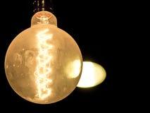 Glühlampe auf schwarzem Hintergrund Stockbilder