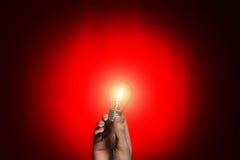 Glühlampe in der Hand auf rotem Hintergrund Lizenzfreie Stockfotos