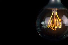 Glühlampe der Retro- Weinlese mit geführter Technologie bult-auf im warmen hellgelben Tönungs- und Schwarzhintergrund, energiespa stockfotos