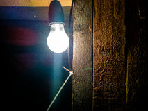 Glühlampe, die in der Dunkelheit hinaufklettert Lizenzfreie Stockfotos