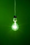 Glühlampe, die gegen grünen Hintergrund hängt Stockbilder