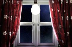 Glühlampe, die im Fenster glänzt Stockfotografie