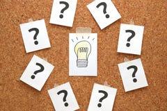 Glühlampe gezeichnet auf ein Weißbuch mit vielen Fragezeichen Stockfotografie