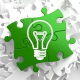 Glühlampe-Ikone auf grünem Puzzlespiel. Stockfotos