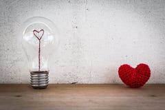 Glühlampe mit Herz-geformtem Faden und rotes Herz-geformter Seide Stockfotos