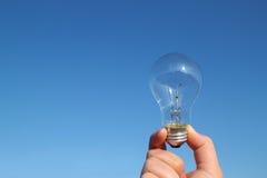 Glühlampe und die Hand im blauen Himmel Stockbilder