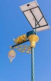Glühlampe und Solarenergie der goldenen Kuh mit Hintergrund des blauen Himmels Lizenzfreie Stockbilder