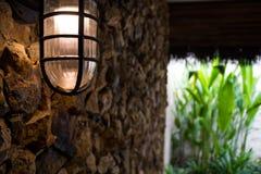 Glühlampedekoration der Weinleseart auf Steinwand Stockfotografie