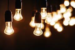 Glühlampen über dunkler Beschaffenheit lizenzfreie stockfotos