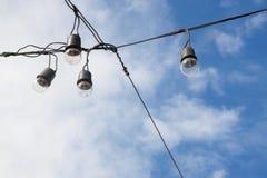 Glühlampen auf dem Hintergrund des blauen Himmels, elektrisch stockfotografie