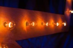 Glühlampen auf einem hölzernen Hintergrund als Element des Dekors Lizenzfreie Stockfotos