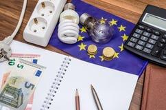 Glühlampen auf europäischen Banknoten mit leerem Notizblock und Stift, Taschenrechner Stockbild
