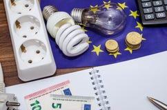 Glühlampen auf europäischen Banknoten mit leerem Notizblock und Stift, Taschenrechner Stockfotos