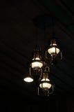 Glühlampen auf schwarzem hölzernem Hintergrund Stockfotos