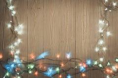 Glühlampen des fantastischen Blinkers oder Girlanden und Kranz auf hölzerner Tabelle f Stockfotografie