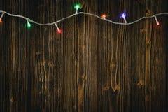 Glühlampen des fantastischen Blinkers oder Girlanden und Kranz auf hölzerner Tabelle f Stockbild