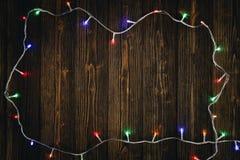Glühlampen des fantastischen Blinkers oder Girlanden und Kranz auf hölzerner Tabelle f Stockbilder