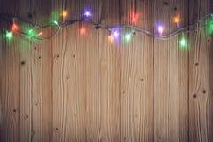 Glühlampen des fantastischen Blinkers oder Girlanden und Kranz auf hölzerner Tabelle f Lizenzfreie Stockfotos
