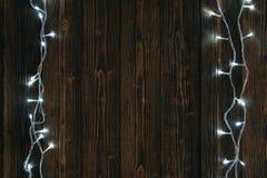 Glühlampen des fantastischen Blinkers oder Girlanden und Kranz auf hölzerner Tabelle f Lizenzfreies Stockbild