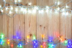 Glühlampen des fantastischen Blinkers oder Girlanden und Kranz auf hölzerner Tabelle f Lizenzfreie Stockbilder