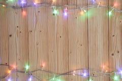 Glühlampen des fantastischen Blinkers oder Girlanden und Kranz auf hölzerner Tabelle f Stockfotos