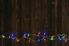 Glühlampen des fantastischen Blinkers oder Girlanden und Kranz auf hölzerner Tabelle f Stockfoto