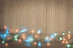 Glühlampen des fantastischen Blinkers oder Girlanden und Kranz auf hölzerner Tabelle f Lizenzfreie Stockfotografie