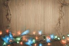 Glühlampen des fantastischen Blinkers oder Girlanden und Kranz auf hölzerner Tabelle f Lizenzfreies Stockfoto