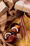 Glühwein im Glasbecher mit Gewürzen Weihnachtsheißes Getränk auf Holztisch mit Handwerksgeschenken stockfotografie