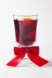 Glühwein im Glasbecher verziert mit einem roten Bogen lizenzfreies stockfoto