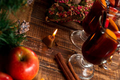 Glühwein mit Früchten, Kerzen, Gewürze auf Holztisch Weihnachten GETRÄNK-Rezeptbestandteile des Winters Erwärmungsherum Zwei Scha stockfotografie
