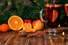 Glühwein mit Früchten und Gewürzen auf Holztisch Weihnachtsdekorationen im Hintergrund GETRÄNK-Rezeptbestandteile des Winters Erw stockbilder