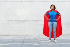 Gl?ckliche Afroamerikanerfrau im roten Kap des Superhelden lizenzfreie stockbilder