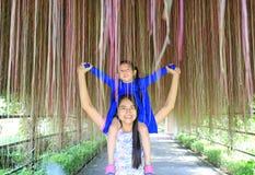 Gl?ckliche asiatische Mutter und Tochter unter sch?ner Wurzel des Banyanbaumes stockbilder