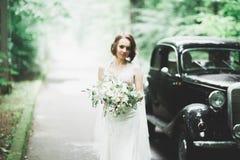 Gl?ckliche Braut im Retro- Auto, das an ihrem S?uberntag aufwirft stockfotos